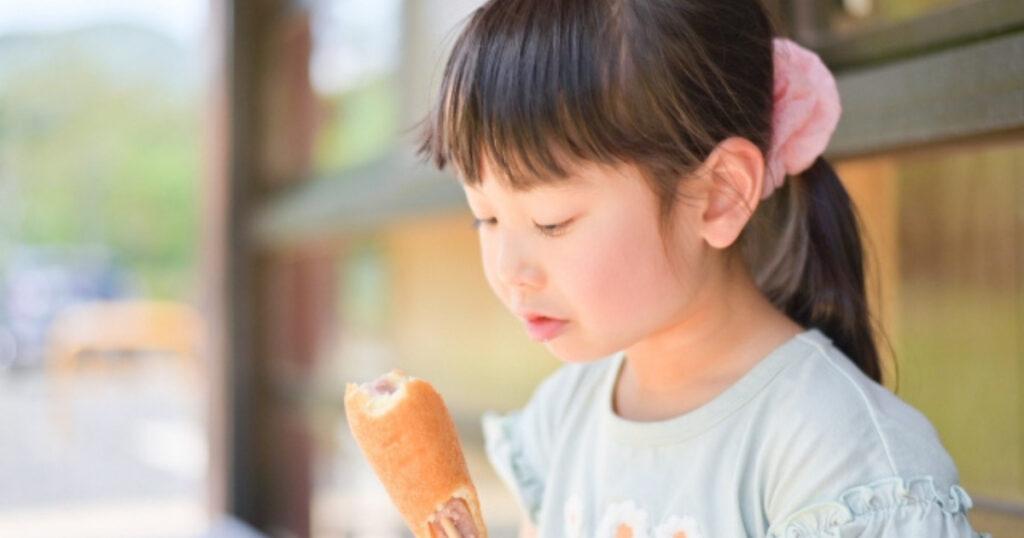 アメリカンドッグを食べる女の子
